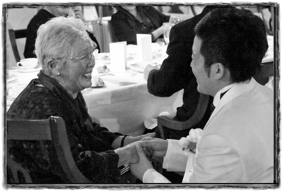 結婚式場でおばあちゃんと握手する新郎