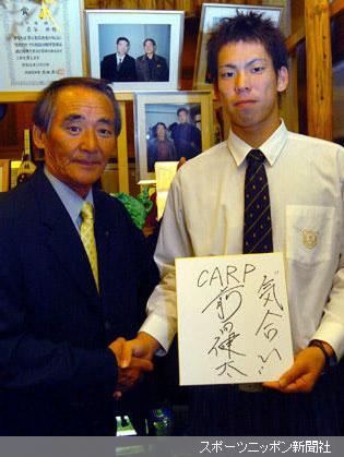 入団に合意したPL学園・前田(右)は、大先輩・桑田の記念写真の前で、宮本スカウトとガッチリ握手