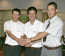 出発前に、手を握り合う日本高校野球選抜チームの(左から)斎藤投手、後藤主将、田中投手=29日午前、成田空港