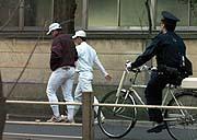 〔写真:ロードワークから帰る斎藤(右)。巡回中のおまわりさんに見守られる形となった〕