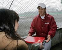 女性報道陣からチョコをもらう斎藤佑樹=東伏見の早大グラウンド