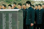 早大OBが刻銘された碑を見る早実の斎藤佑樹投手(右から2人目)=3日午後、糸満市の平和祈念公園