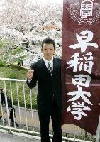 入学式を終え、満開の桜をバックに決意を新たにする斎藤佑樹(代表撮影)