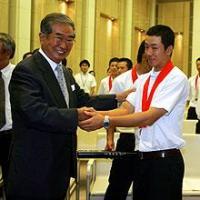 石原都知事(左)に右腕をもまれ恐縮した表情を見せる早実の斎藤投手