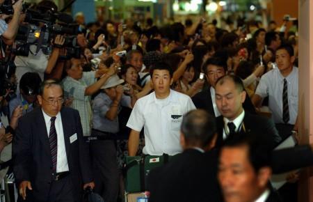 空港に集まった大勢のファンから声援を受け、驚きの表情を見せる早実の斎藤投手(中央)ら
