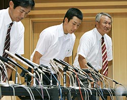 記者会見を終え一礼する早実高の斎藤佑樹投手。右は野球部の和泉実監督=11日午後、東京都国分寺市の同校
