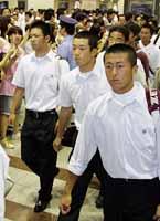大勢のファンの出迎えを受けた早実のエース斎藤(右から2人目)は、マウンドでも見せなかった緊張の顔=22日午後2時30分、JR東京駅