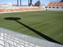 冬の晴天。照明塔の長い影が芝生に伸びる。NACK5スタジアム大宮。