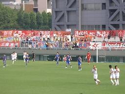 西が丘サッカー場でサッカーJFLを観戦。終了間際にHONDA FCが決勝点、暫定首位に。スタンドにはJクラブ以上の数の横断幕。背後は国立スポーツ科学センターの建物。