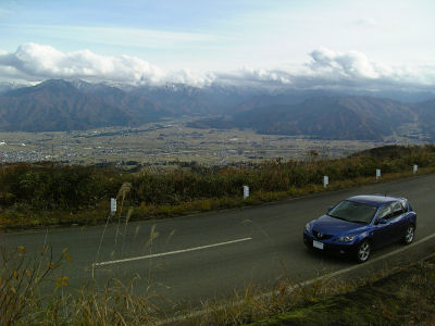 マツダアクセラと雪化粧した越後山脈