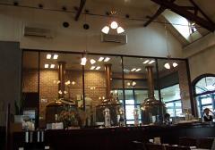 ガラス越しに醸造タンクが見えます ・・・ちゃんと使っていたよ! 右奥にルームテラス席とカウンターがあります。