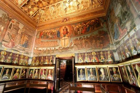 聖書のシーンが描かれた壁と肖像画が並んでいるカテドラルの参事会室(トレド)