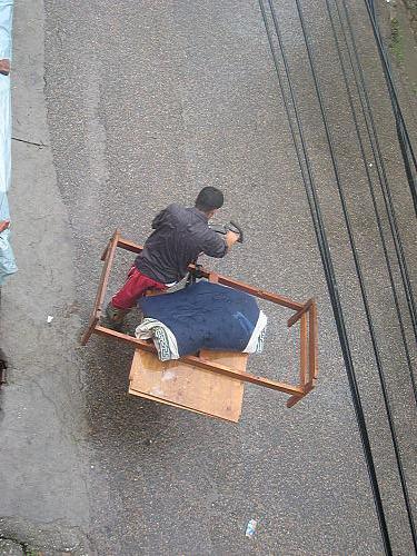 雨の中ベットを自転車で運ぶアパ